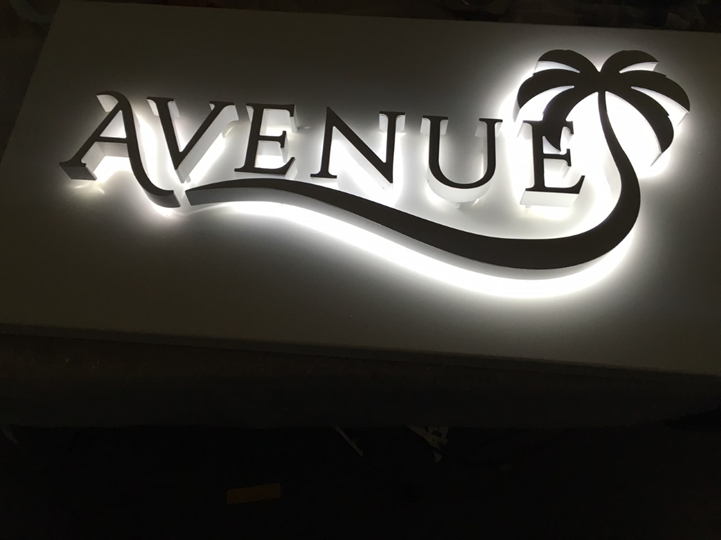 A back-lit Avenue sign featuring their logo