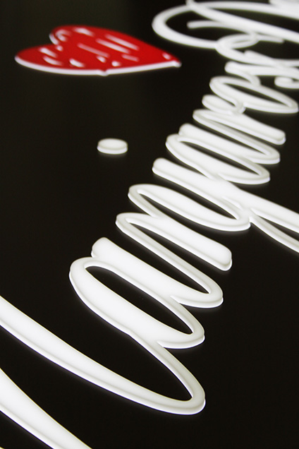 A close up image of a lit Manjaros Desserts sign