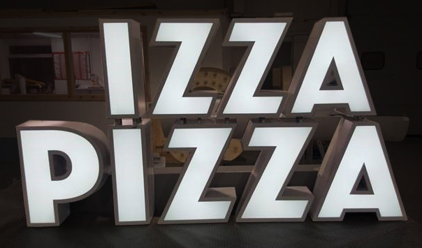 An Izza Pizza sign made using built-up letters